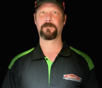 Crew Chief, Lee is wearing a black and green SERVPRO's shirt with a black and red hat on his head.